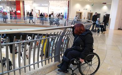Woman in wheelchair browsing rails of clothes in a shop