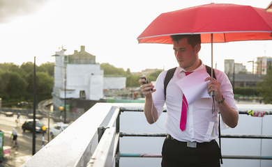 Man holding a red umbrella, looking at a smartphone screen