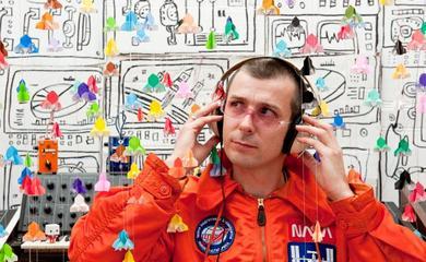 Man in orange jacket wearing headphones