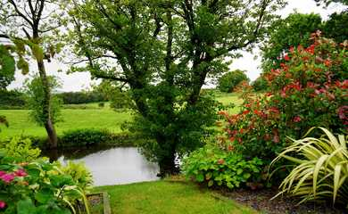 Pretty gardens with lots of green grass, flowers and trees with a stream running through
