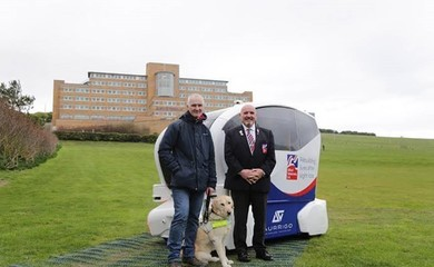 Three Men and a guide dog, stand with an electric pod car on grass, with a large building behind them