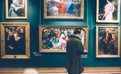 A man stands in an Art Gallery Looking at Paintings