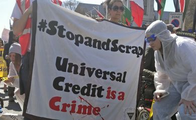 A protester in a crime scene outfit crouches by a sign saying universal credit is a crime