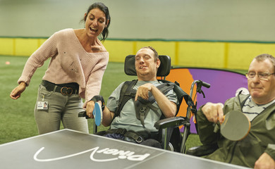 Two men in wheelchairs and a lazy standing up, playing table tennis