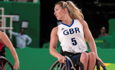 Sophie in her sports wheelchair on a basketball court