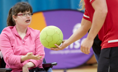 Girl with brown hair and glasses sitting in wheelchair in a sports hall
