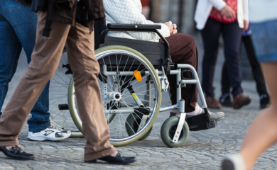 Wheelchair wheels with people walking past