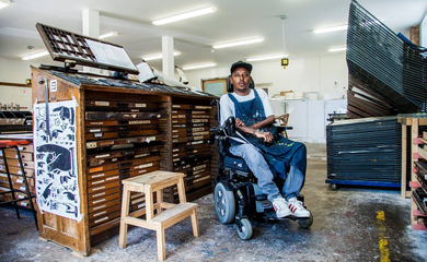 Portrait of Christopher Samuel - black man sitting in a power chair in an art workshop