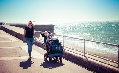 Man in a wheelchair with lady walking beside him along a seafront
