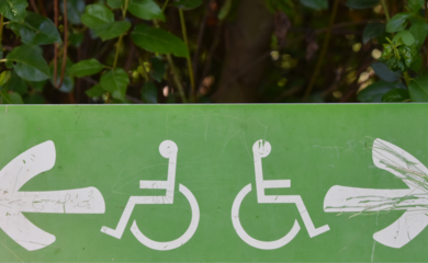 a green sign, has two wheelchairs on it, one facing left, one facing right, two white arrows face left and right