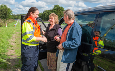 Couple and highways agent standing by a vehicle