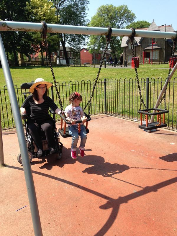 Mum in wheelchair pushing daughter on swing