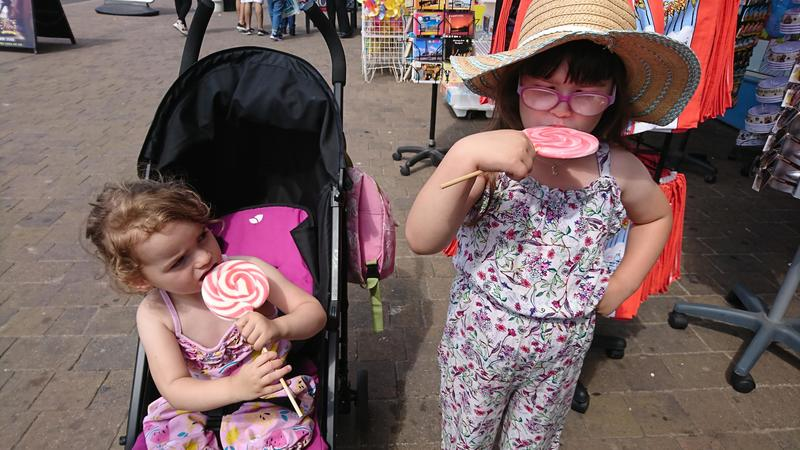 Two little girls eating lolly pops