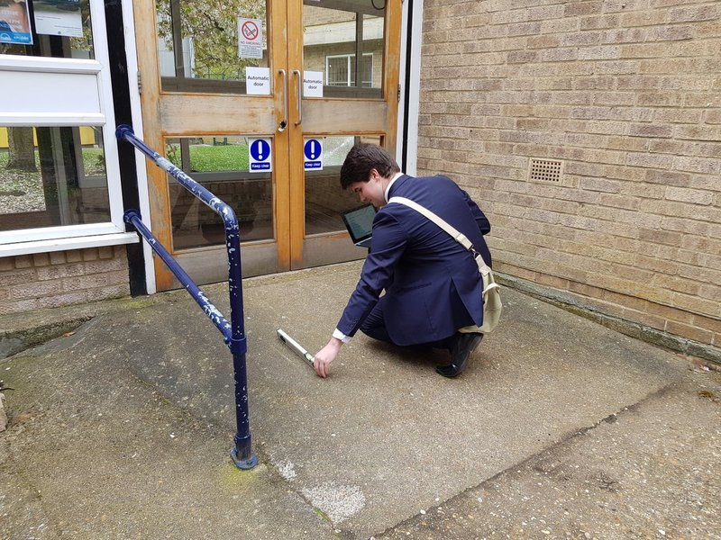 Man measuring ramp gradient with tape measure
