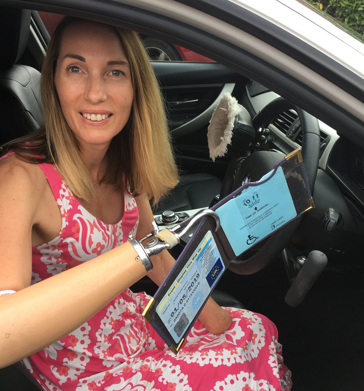 helen dolphin in her car holding her blue badge