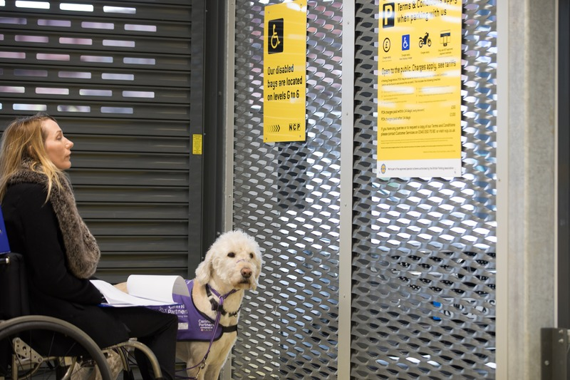 Helen Dolphin in a car park with her assistance dog