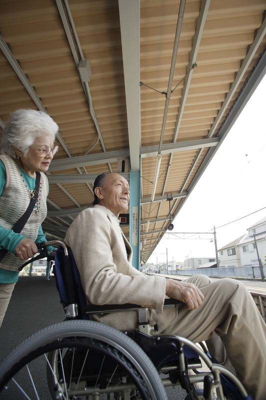 Two older people, one using a wheelchair