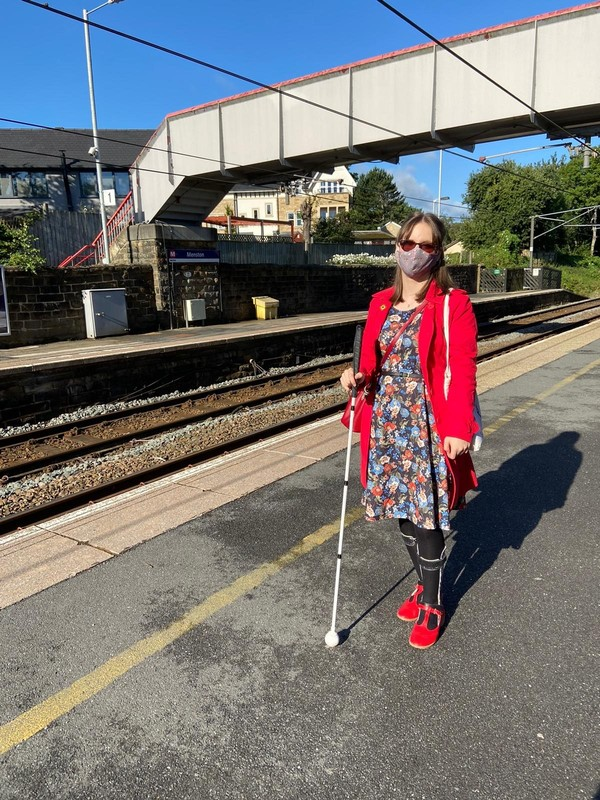 Visually impaired person wearing a mask and using a cane