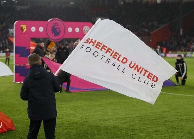 Football fan waving a flag which says Sheffield United Football Club on it