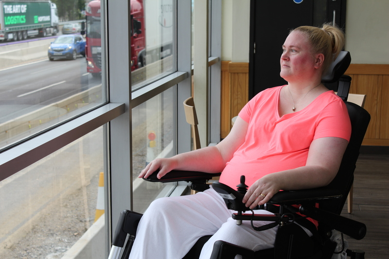Lady with blonde hair wearing a pink t shirt, sitting in a wheelchair looking out of a window