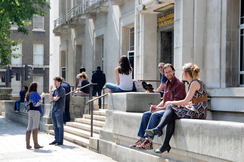 Students sitting on walls and steps outside university building