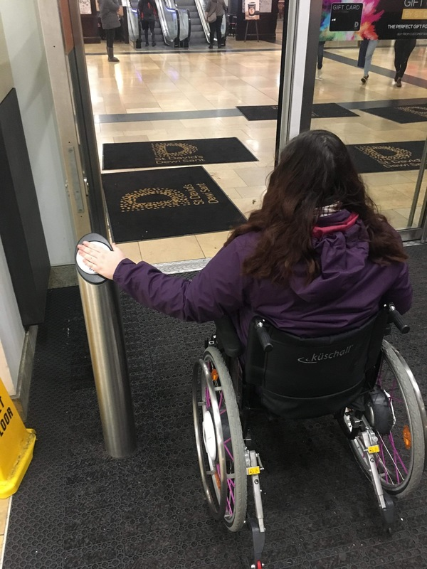 Holly, a white woman has he back to the camera, she is using a push button assist automatic door from her wheelchair, she is wearing a purple coat