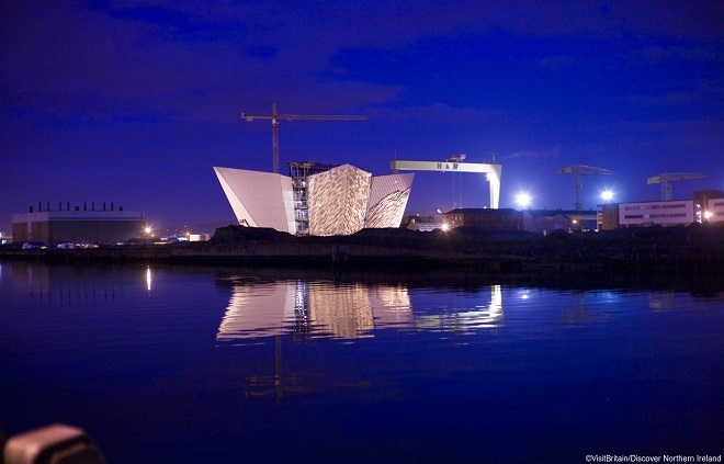 The Titanic memorial in Belfast harbour, lit up against the night sky.